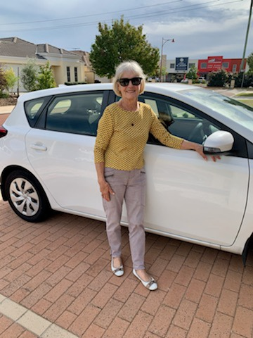 Mature woman leaning against driver side of white car