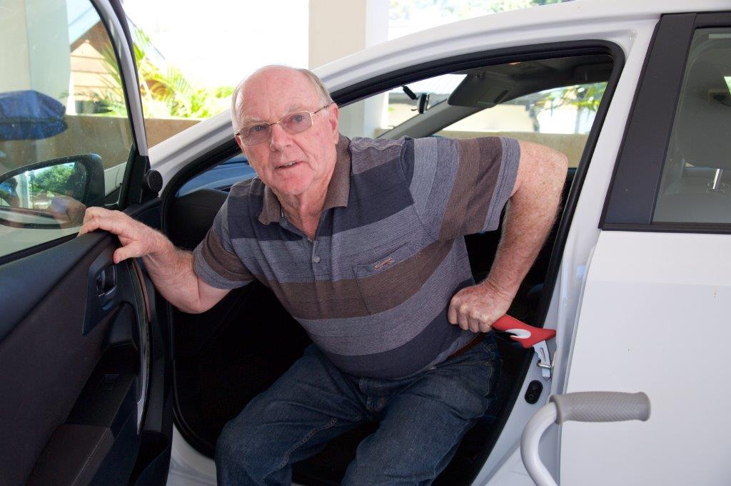 older male using aid to exit vehicle