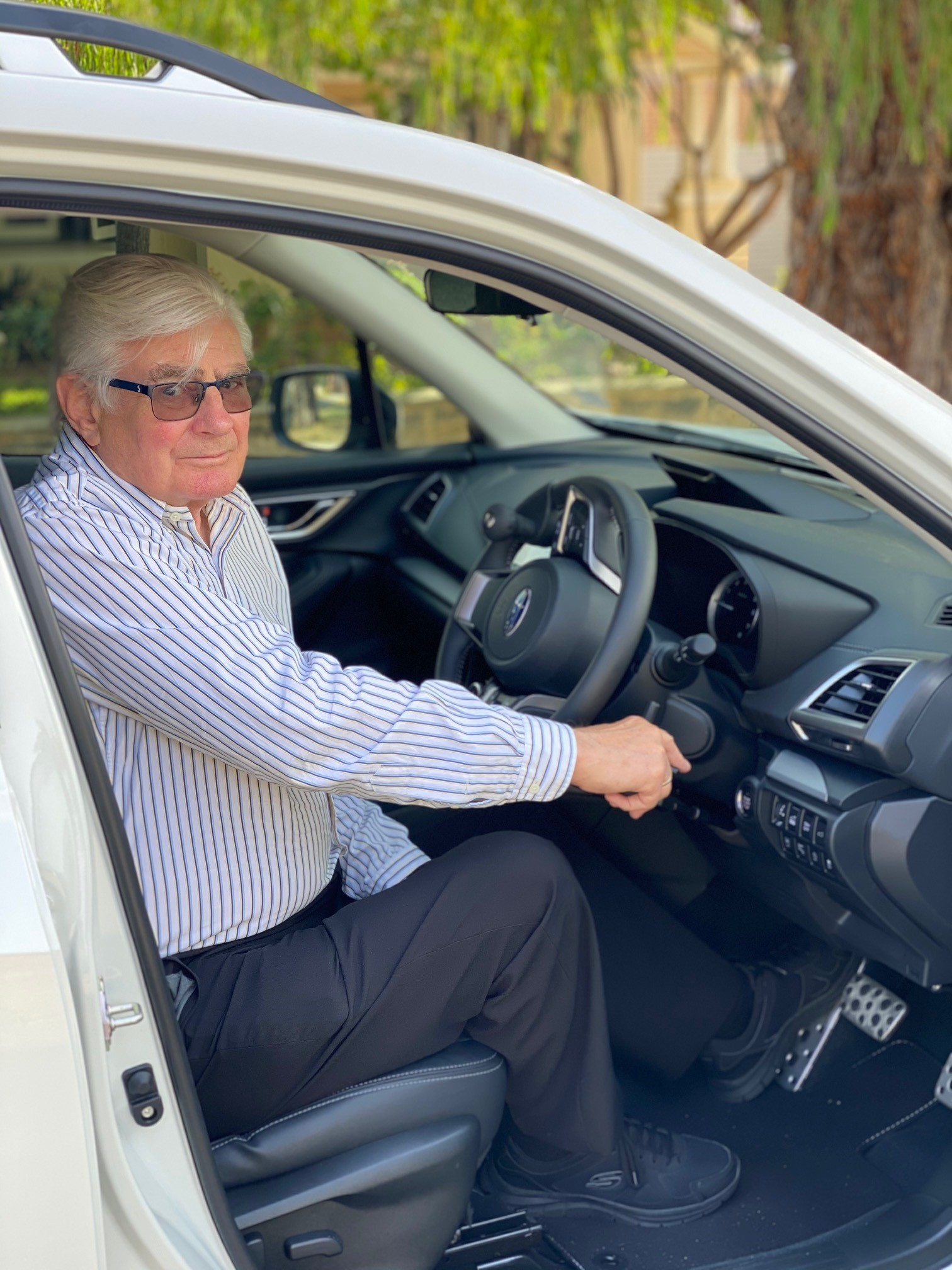 Older male in driver seat of car showing hand controls
