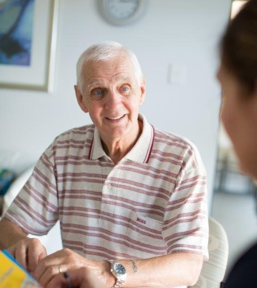 Older man speaking with health professional