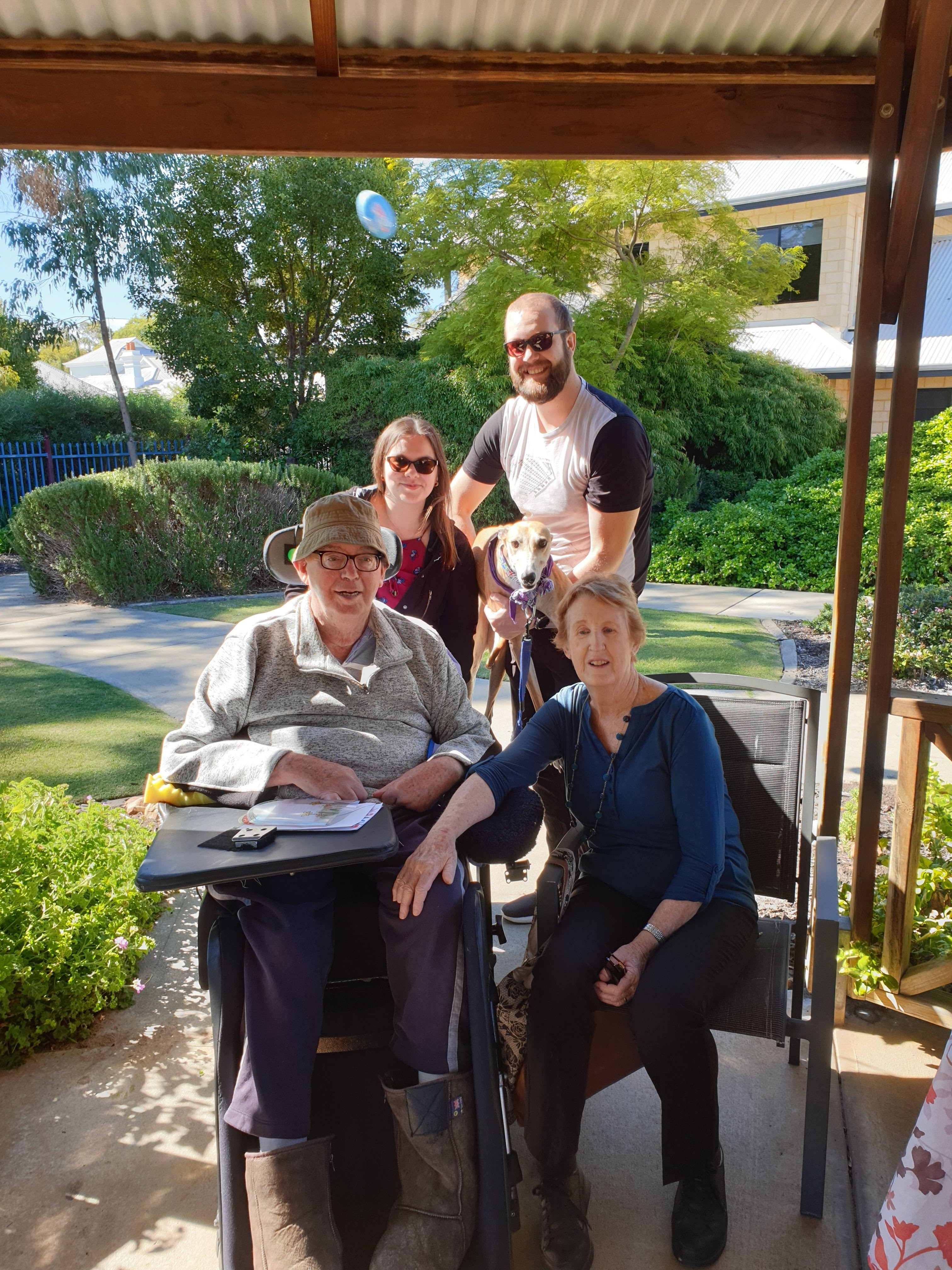 Family of four, 2 males (one in a wheelchair) and 2 females (one seated in a chair next to male in wheelchair) posing outside with their pet greyhound