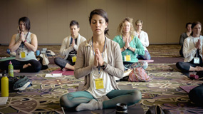 Group of females all with eyes closed in a room meditating