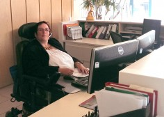 female wearing glasses and a headset in wheelchair at a desk with two computer screens in an office
