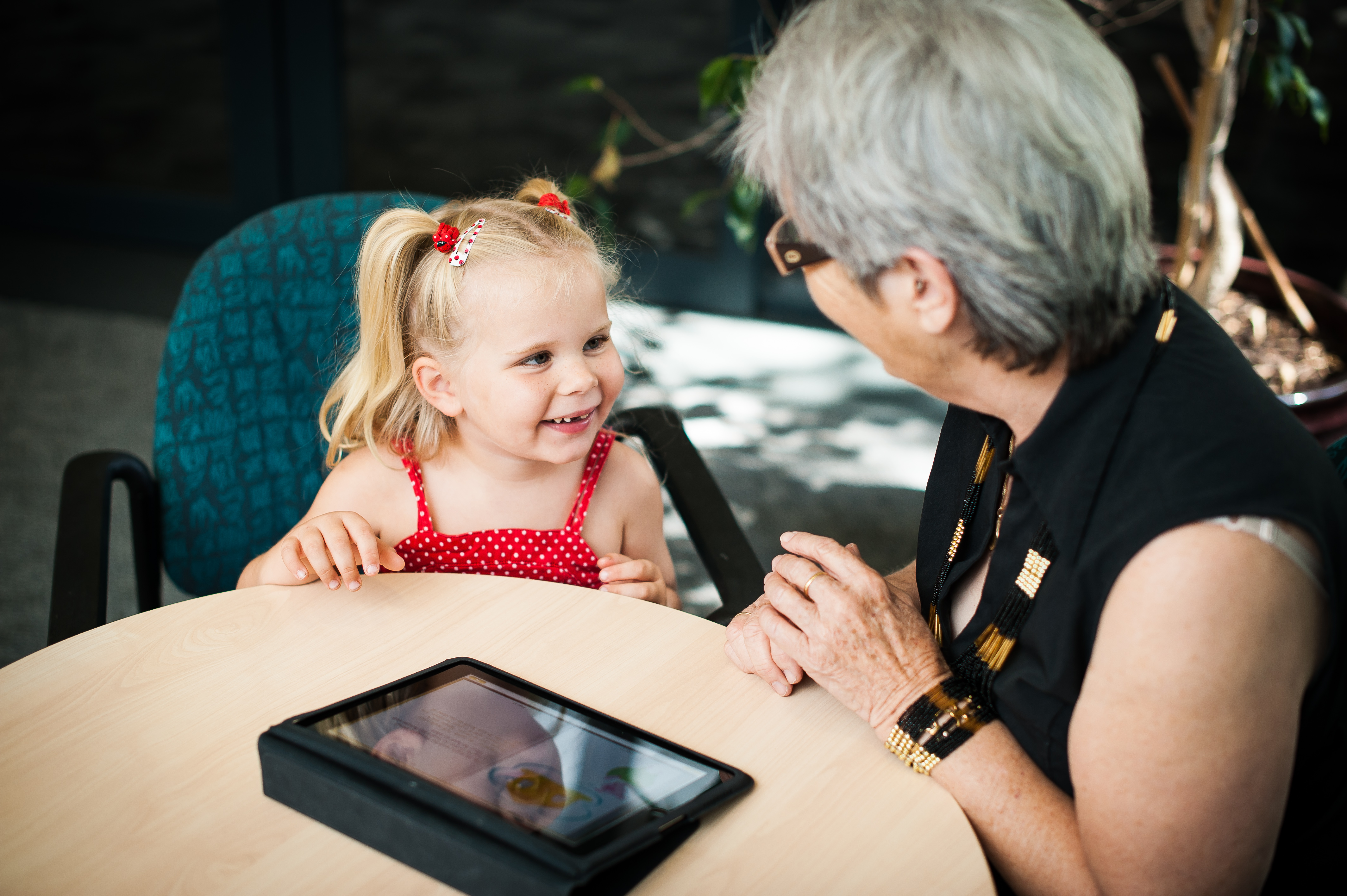 smiling young girl in red dress looking at an older lady in side profile wearing glasses with a tablet on the table
