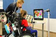 female child in wheelchair with head support and OT standing beside her looking at a mounted computer screen