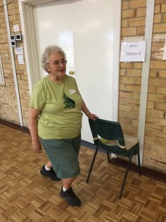 Older female in green top and skirt lunging a holding chair in a hall