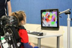 child in red top in a wheelchair with head support staring at a mounted computer screen