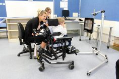 2 adults and a child in a wheelchair with head support  in a classroom positioned in front of a custom mounted computer screen