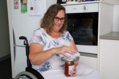 female in a wheelchair opening a jar in front of an oven