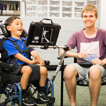 smiling young boy in a blue t-shirt in wheelchair with eye gaze device and a smiling teenage boy in a maroon t-shirt and shorts sitting on a chair
