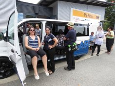 disability modified van in carpark with female in sunglasses sitting in movable passenger chair with female OT by side for support and multiple people in the background