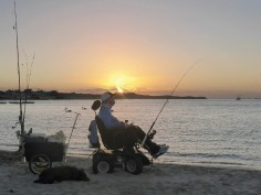 man in powered wheelchair on the beach fishing at sunset