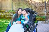 Girl with long black hair hugging young boy in a wheelchair in a park