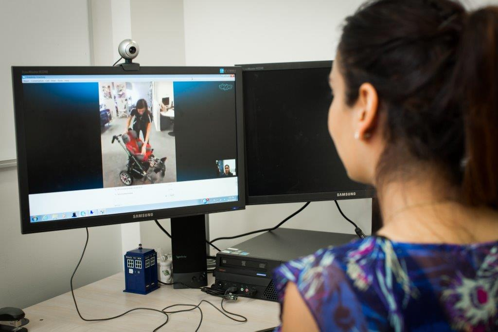 back of a female's head looking at a computer screen showing an Indigo staff member demonstrating assistive technology