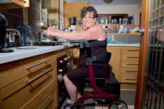 female in black dress sitting on a walking frame in the kitchen doing food preparation