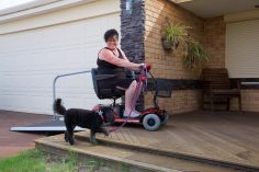 female in a black dress on a red mobility scooter going up at ramp with a black dog by her side