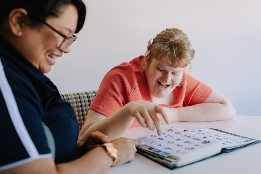 Indigo Speech Pathologist working with a young woman using an AAC device