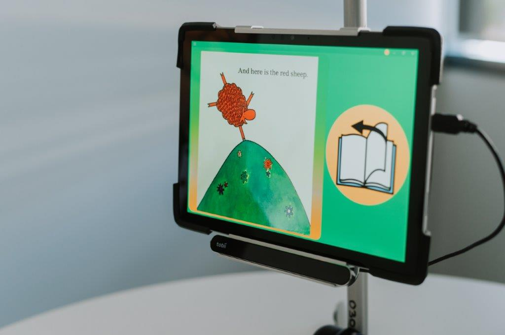 Mounted iPad or table showing AAC program with sheep doing handstand and book on screen