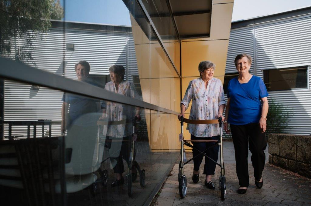 two mature females one with a walker going down a ramp outside