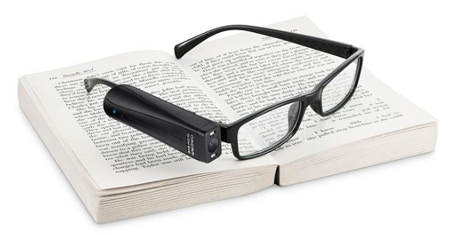 Open book with black reading glasses resting on top