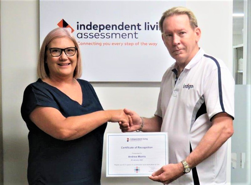 Professional male presenting a certificate to professional female and shaking her hand