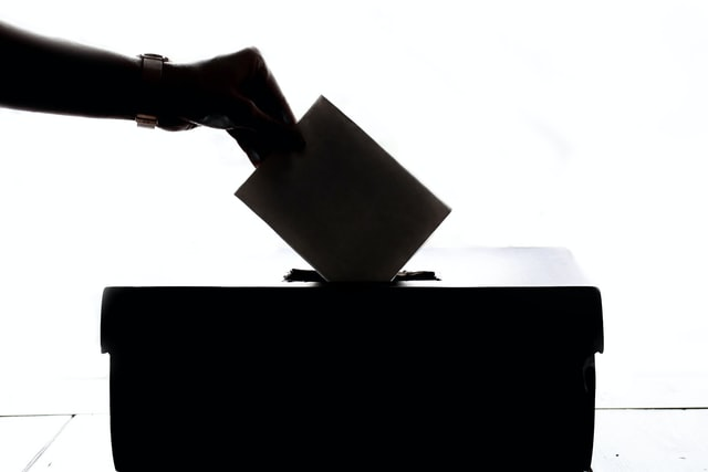 Silhouette of hand placing a vote into a box