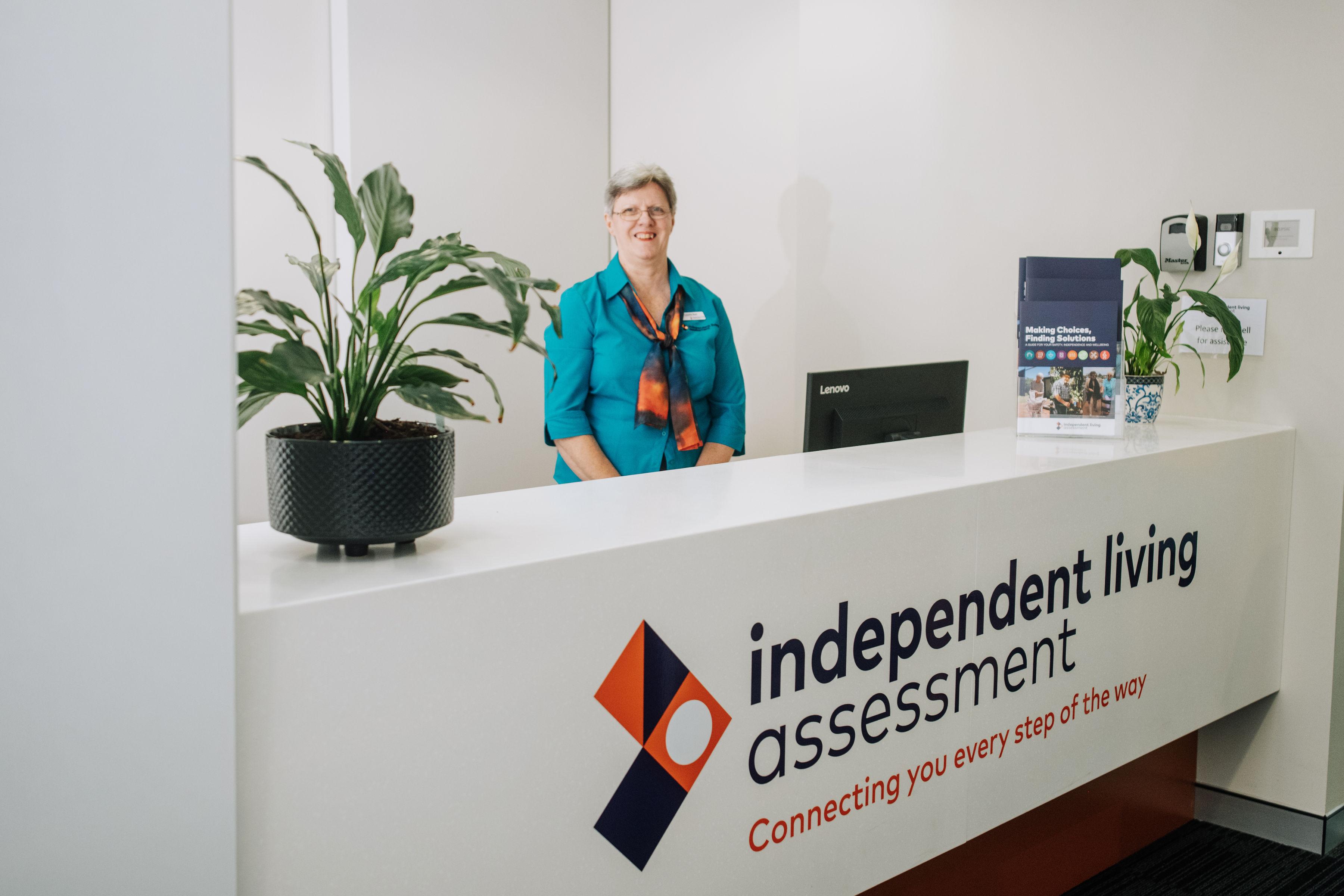 Female ILA professional standing in reception area with ILA signage