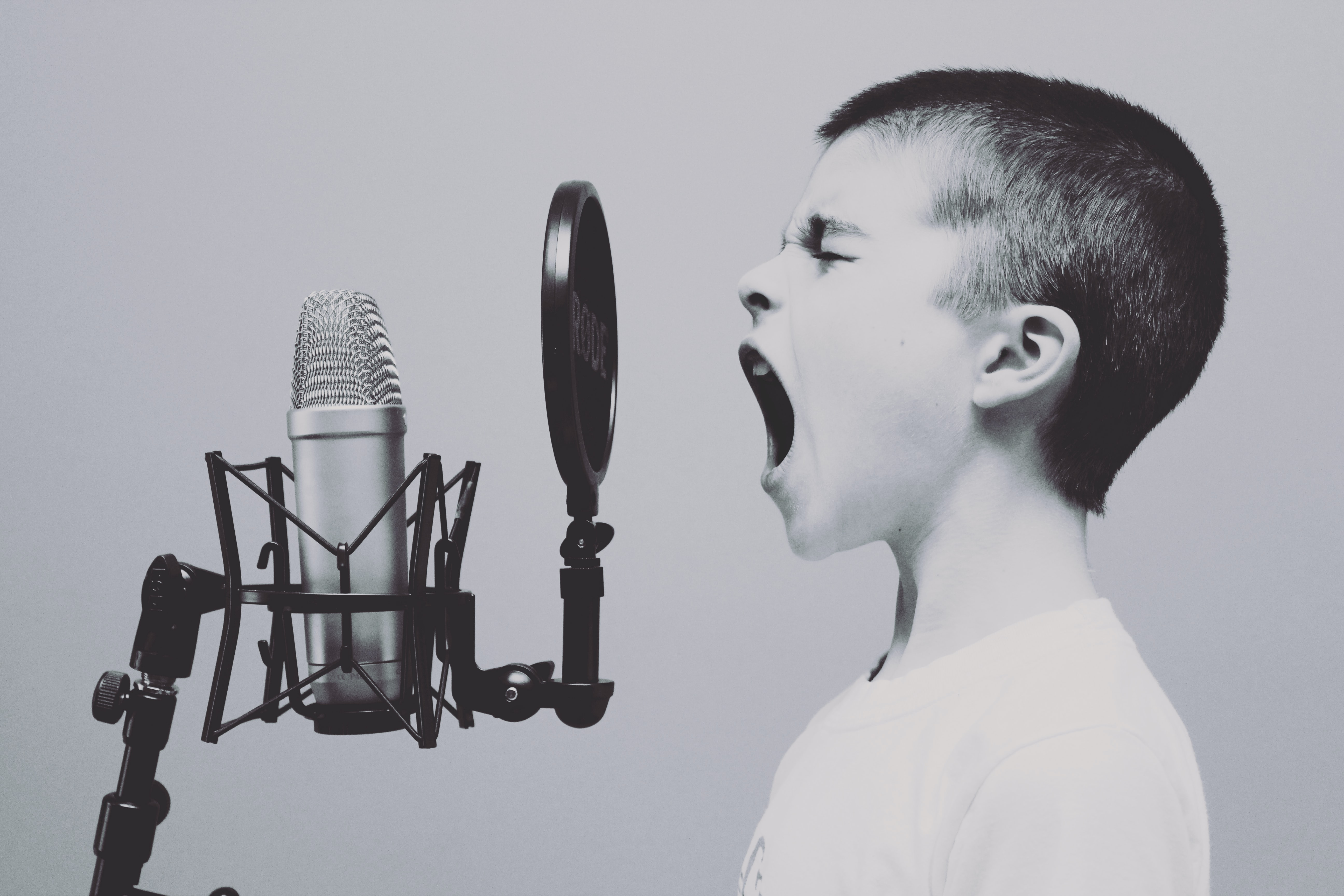 Young boy shouting into a recording microphone