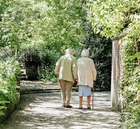 Older couple walking away on a path amongst trees