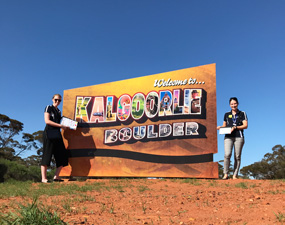 Two Indigo SP's standing at either end of the Kalgoorlie/Boulder sign
